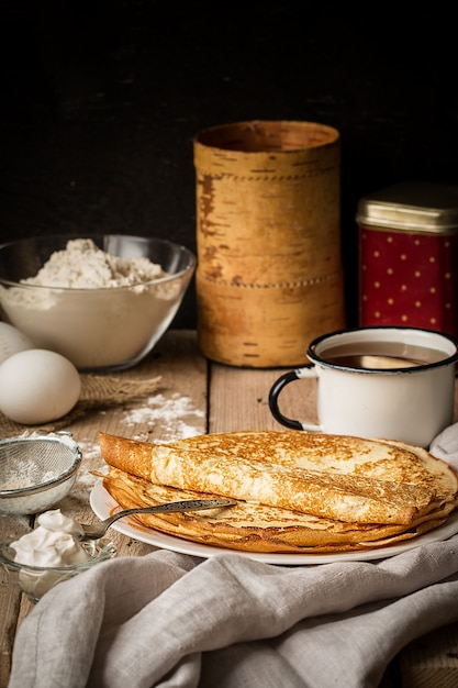 Stack of crepes and ingredients for cooking on a table Premium Photo