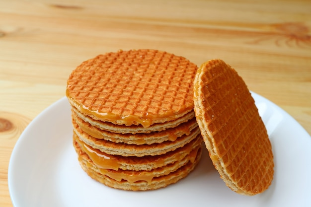 Premium Photo Stack Of Delectable Stroopwafel Or Caramel Filled Dutch Waffle Served On White Plate On Wooden Table