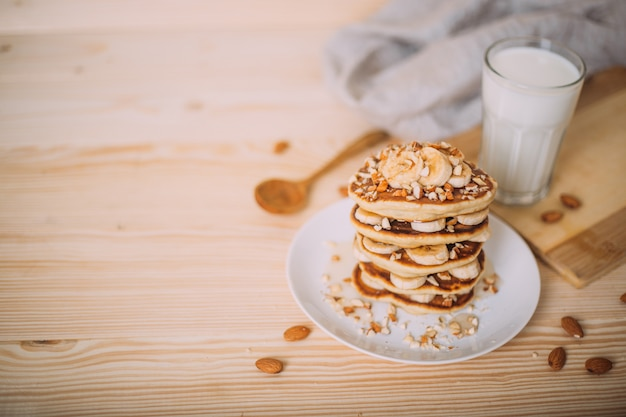 Stack of delicious pancakes with honey, nuts and slices of banana. Premium Photo