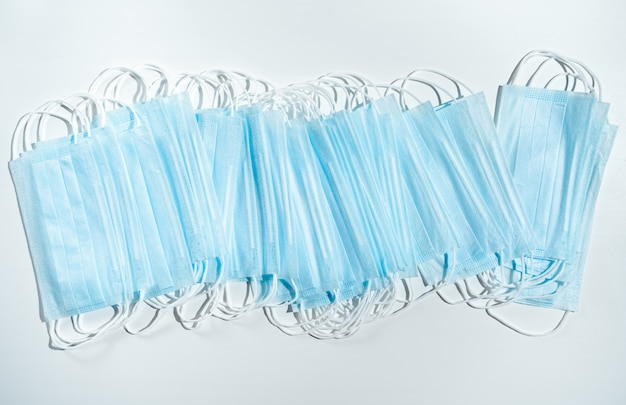 Stack of disposable medical masks on a blue background. face mask for protection virus, flu, coronavirus, covid-19. medical equipment. pharmaceutical background. Premium Photo