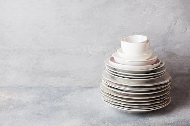Stack of empty clean plates on a gray table with copy space. Premium Photo