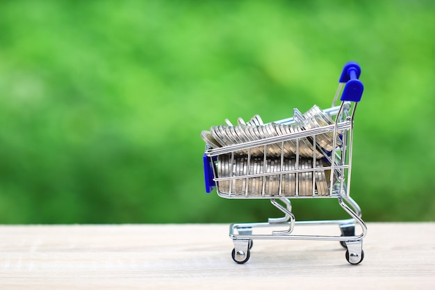 Stack of gold coins money in mini shopping cart Premium Photo