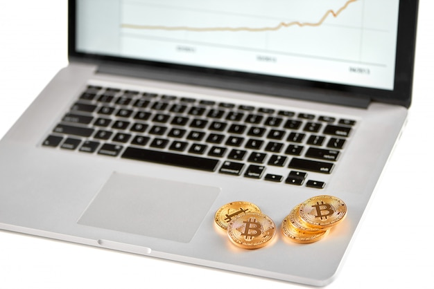 Stack of golden bitcoins placed on silver laptop with blurred financial chart on its screen. Premium Photo