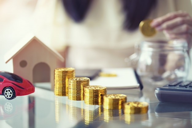 Stack of golden coin with wooden house Premium Photo