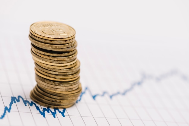 Stack of golden coins over the stock market graph on single line paper Free Photo