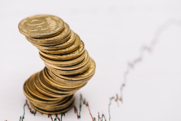 Stack of golden coins over the stock market graph Free Photo