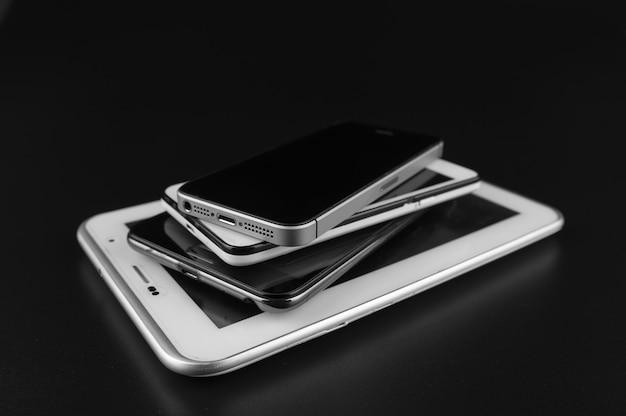 Stack of high-end smartphones on black desk. Premium Photo