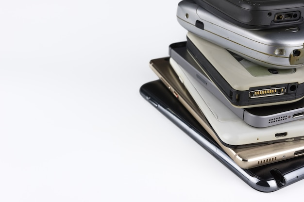 Stack of high-end smartphones on white desk. Premium Photo