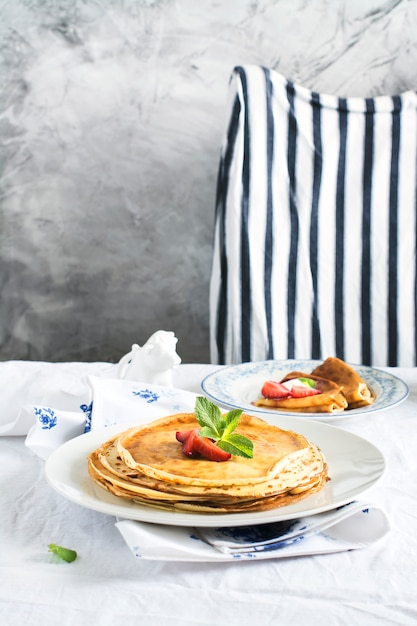 Stack of hot crepes over kitchen table Premium Photo