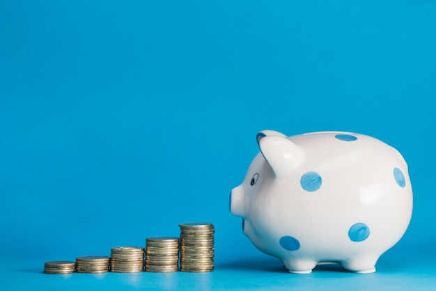 Stack of increasing coins with ceramic piggybank against white backdrop Free Photo