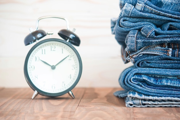Stack of jeans and classic timepieces on old wooden Premium Photo