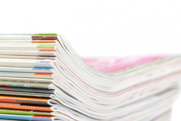 A stack of magazines on a white wall. close-up. Premium Photo