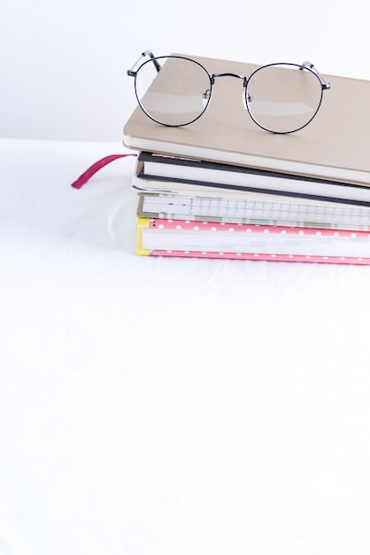 Stack of note books for notes and annotations with glasses on the top on a white table. Premium Photo