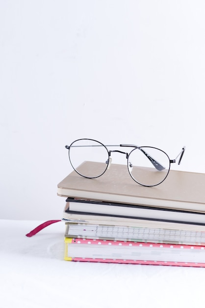 Stack of note books for notes and annotations with glasses on the top on a white table Premium Photo