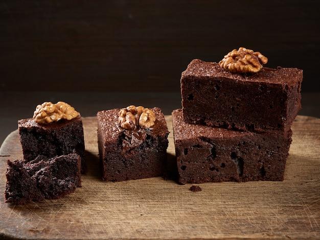 Стек запеченных кусочков шоколадного торта брауни с орехами на деревянной доске Premium Фотографии