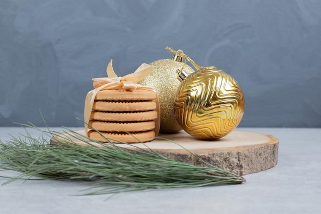 木の板にリボンとクリスマスボールで結ばれたビスケットのスタック。高品質の写真 無料写真