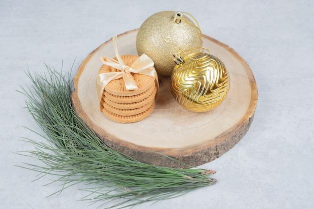 비스킷의 스택 나무 보드에 리본과 크리스마스 볼으로 묶여. 고품질 사진 무료 사진
