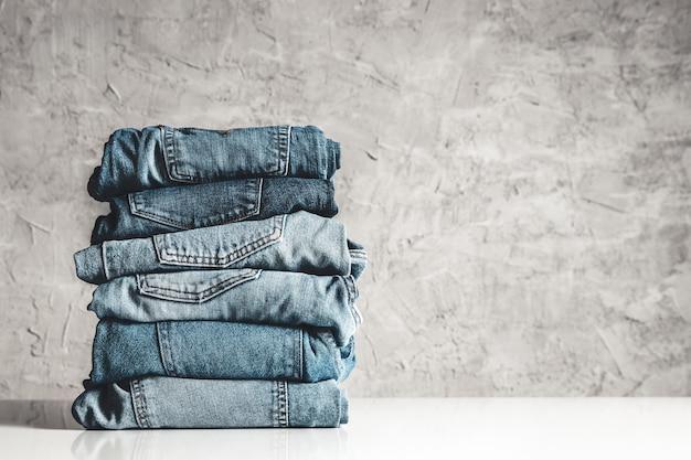 Стек синих джинсов на сером фоне Premium Фотографии