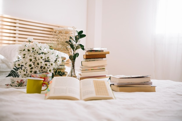 Stack of books and flowers on bed Free Photo