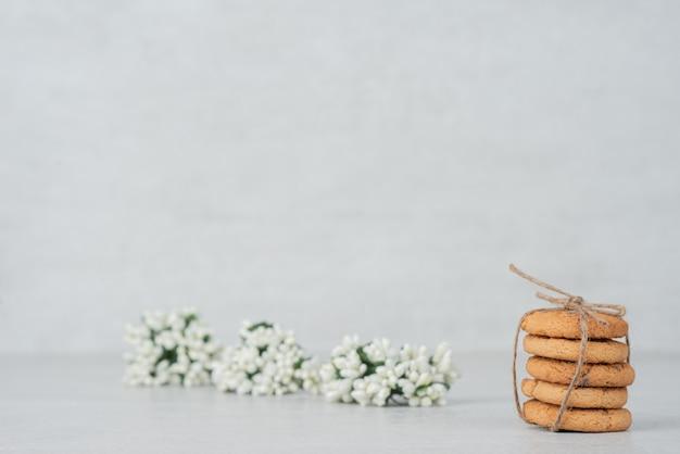 白い表面に白い花とクッキーのスタック。 無料写真