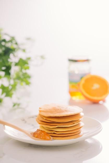 Стек вкусных блинов на тарелке, изолированные на белом фоне Premium Фотографии