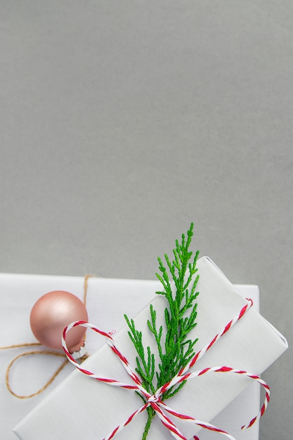 빨간 리본 녹색 주 니 퍼 나뭇 가지 공에 묶여 우아한 흰색 선물 상자 스택 프리미엄 사진