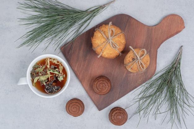 灰色のテーブルにお祝いのビスケットとお茶のスタック。高品質の写真 無料写真