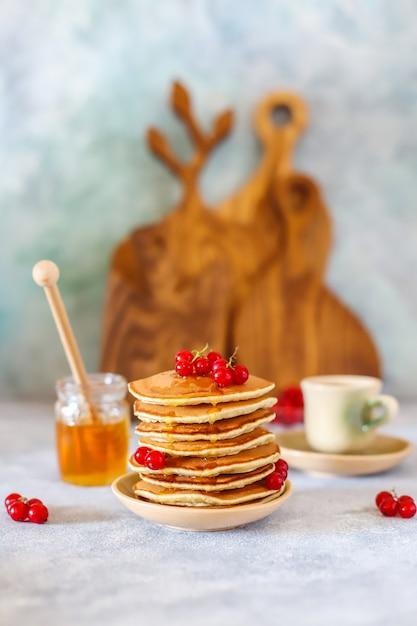 Стек домашние блины с медовым сиропом и ягодами. Бесплатные Фотографии