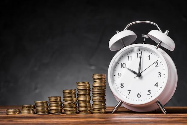 검은 배경에 나무 책상에 흰색 알람 시계와 동전을 증가의 스택 무료 사진