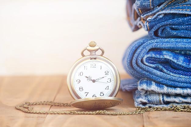 Стек джинсов и классических часов на старом деревянном Premium Фотографии