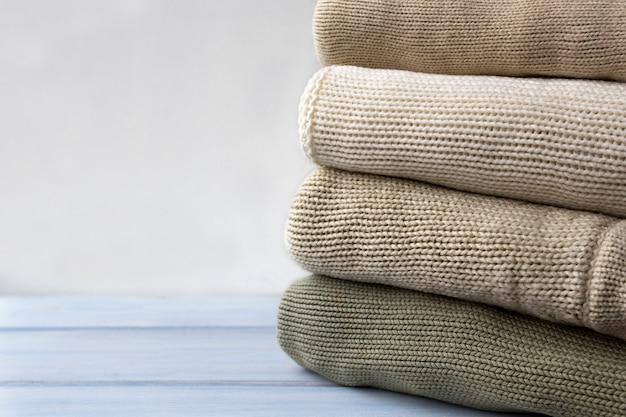 Стог вязаных шерстяных свитеров на светлом деревянном столе. Premium Фотографии