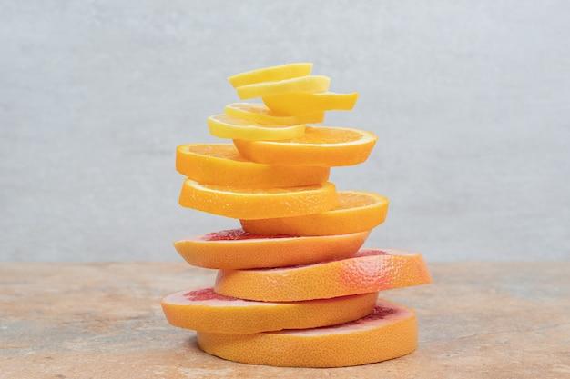 대리석 테이블에 레몬, 오렌지, 자몽 조각의 스택. 고품질 사진 무료 사진