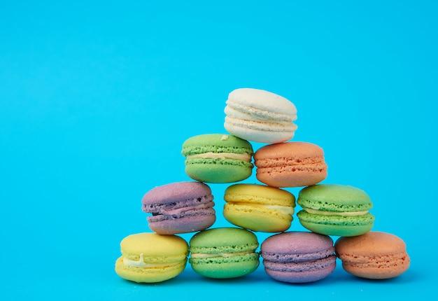 青色の背景にマルチカラーラウンド焼きマカロンケーキのスタック Premium写真