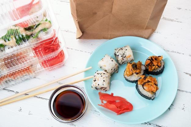寿司ロールセット付きプラスチックボックス、ロールプレート、紙袋のスタック。食品配達 Premium写真