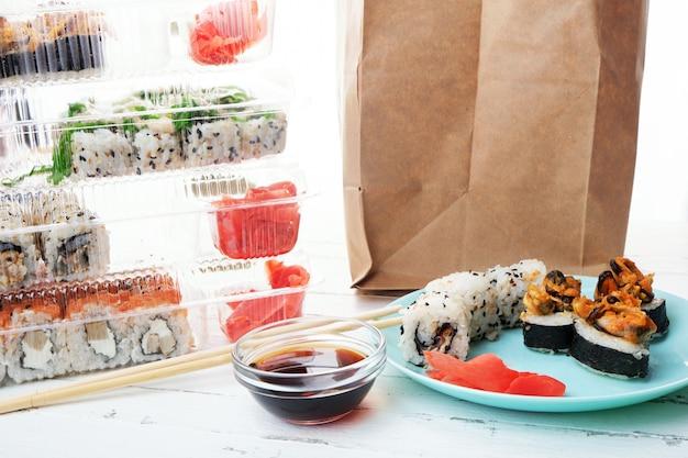 寿司ロールセット付きプラスチックボックスのスタック、ロールと紙袋付きプレート Premium写真
