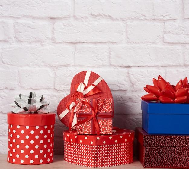 Стек различных коробок с подарками на белой кирпичной стене Premium Фотографии
