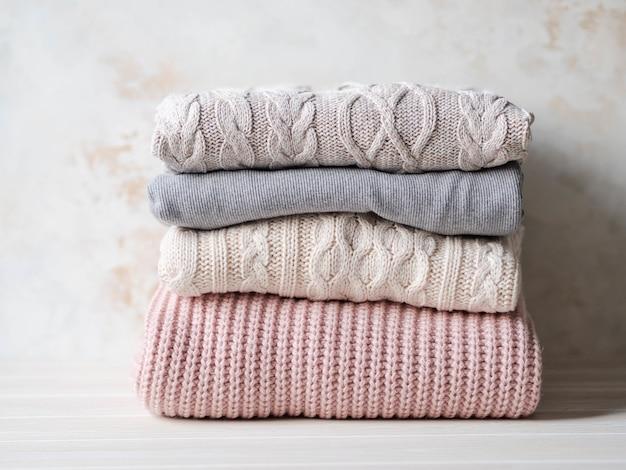 Стек теплых вязаных шерстяных свитеров пастельных оттенков на бежевой фактурной стене. копировать пространство Premium Фотографии
