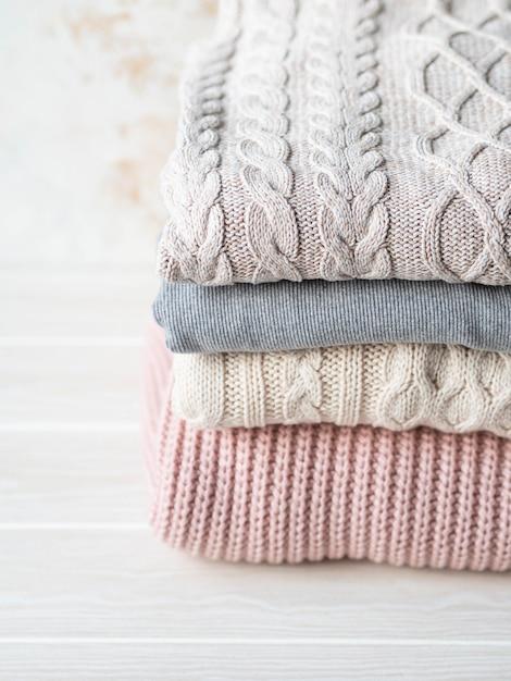 Стек теплых вязаных шерстяных свитеров пастельных оттенков на бежевой фактурной стене. Premium Фотографии