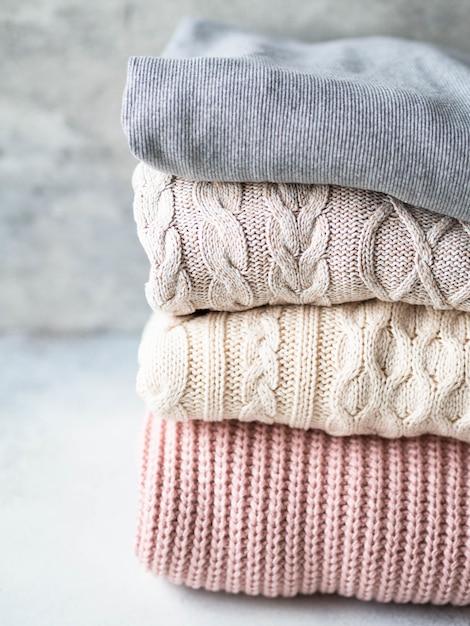 Стек теплых вязаных шерстяных свитеров пастельных оттенков на фоне серой стены. Premium Фотографии