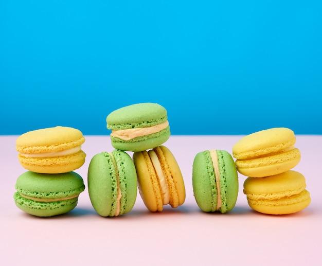 Стек желтых и зеленых круглых миндальных тортов макароны с кремом на синем пространстве Premium Фотографии