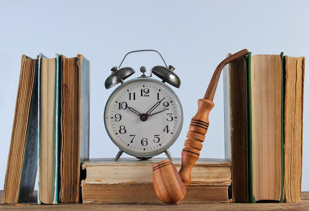 Stack of old books, smoking pipe and alarm clock on woden shelf against the white wall Premium Photo