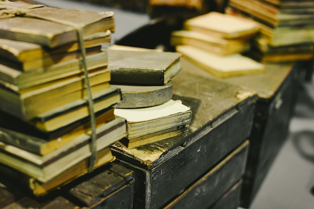 Stack of old books stored in disrepair on an old vintage trunk. Premium Photo