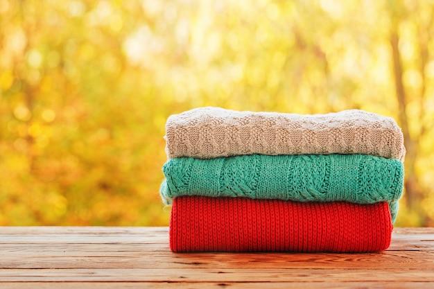 屋外の自然にニットの秋服の山をスタックします。 Premium写真