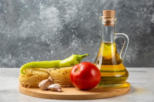 Pila di nidi di pasta cruda, bottiglia di olio d'oliva e verdure sulla tavola bianca. Foto Gratuite