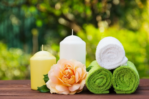 Stack of rolled towels, candles and fragrant roses. Premium Photo