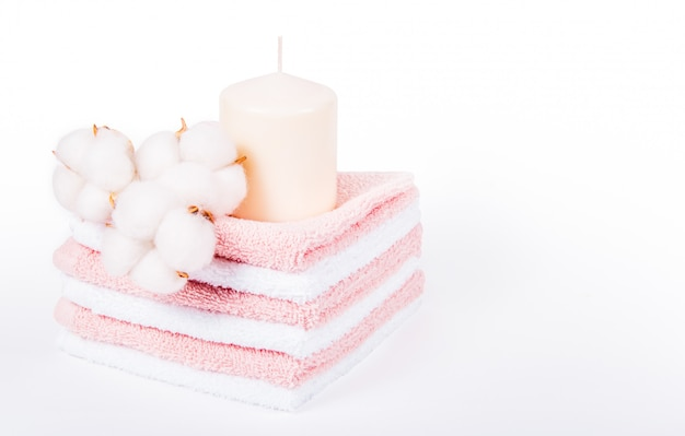Stack of soft towels, candle and cotton flowers Premium Photo