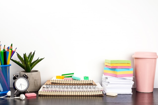 Stack of spiral notebooks and colored stickers, next to a ceramic pot with a flower Premium Photo