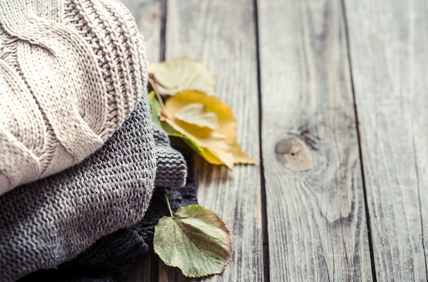 A stack of sweaters and autumn leaves Free Photo