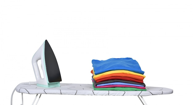 Stack of tidy clothes and a iron on ironing board Premium Photo