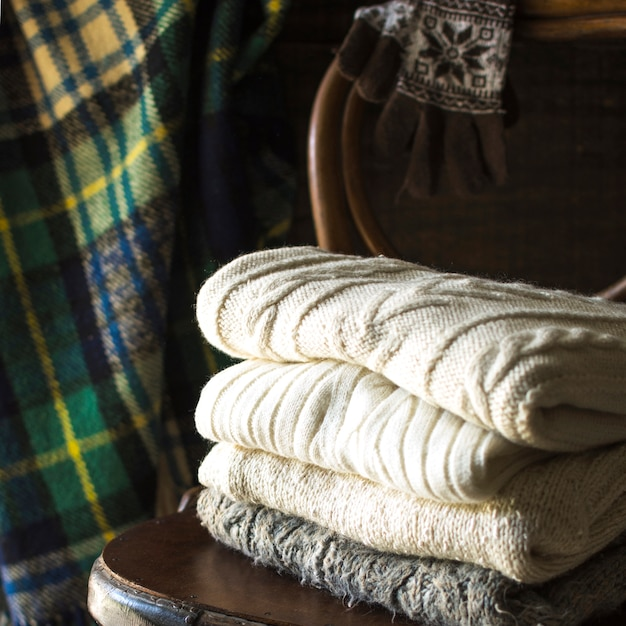 Stack of warm clothes on chair Free Photo